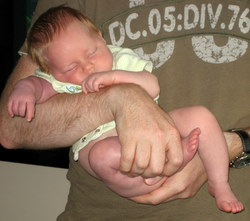 6 weeks - asleep in dad's arms with a bare bum